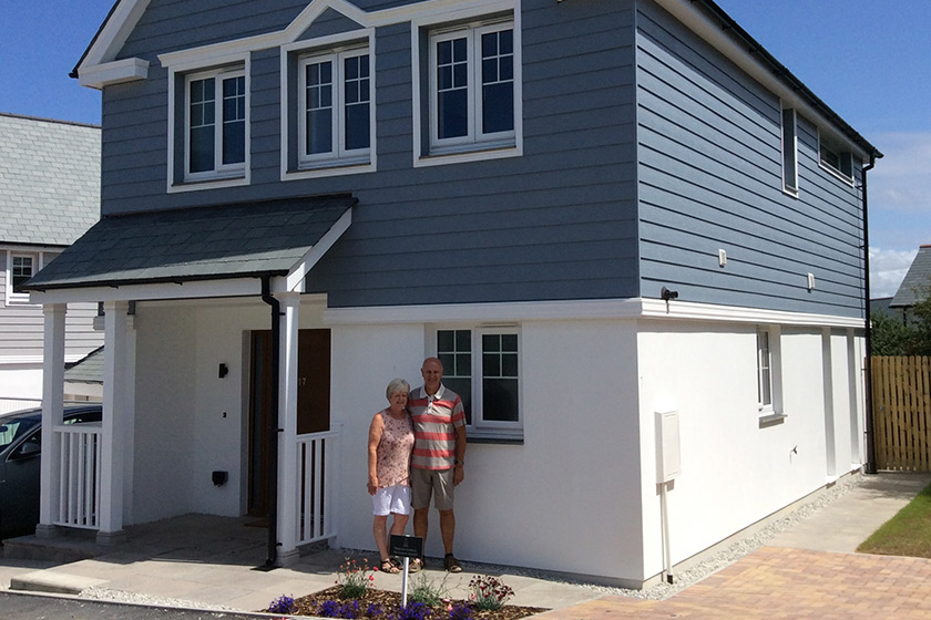 Colin and Janet Walker posing in front of their new home at Hawkers Reach in Padstow