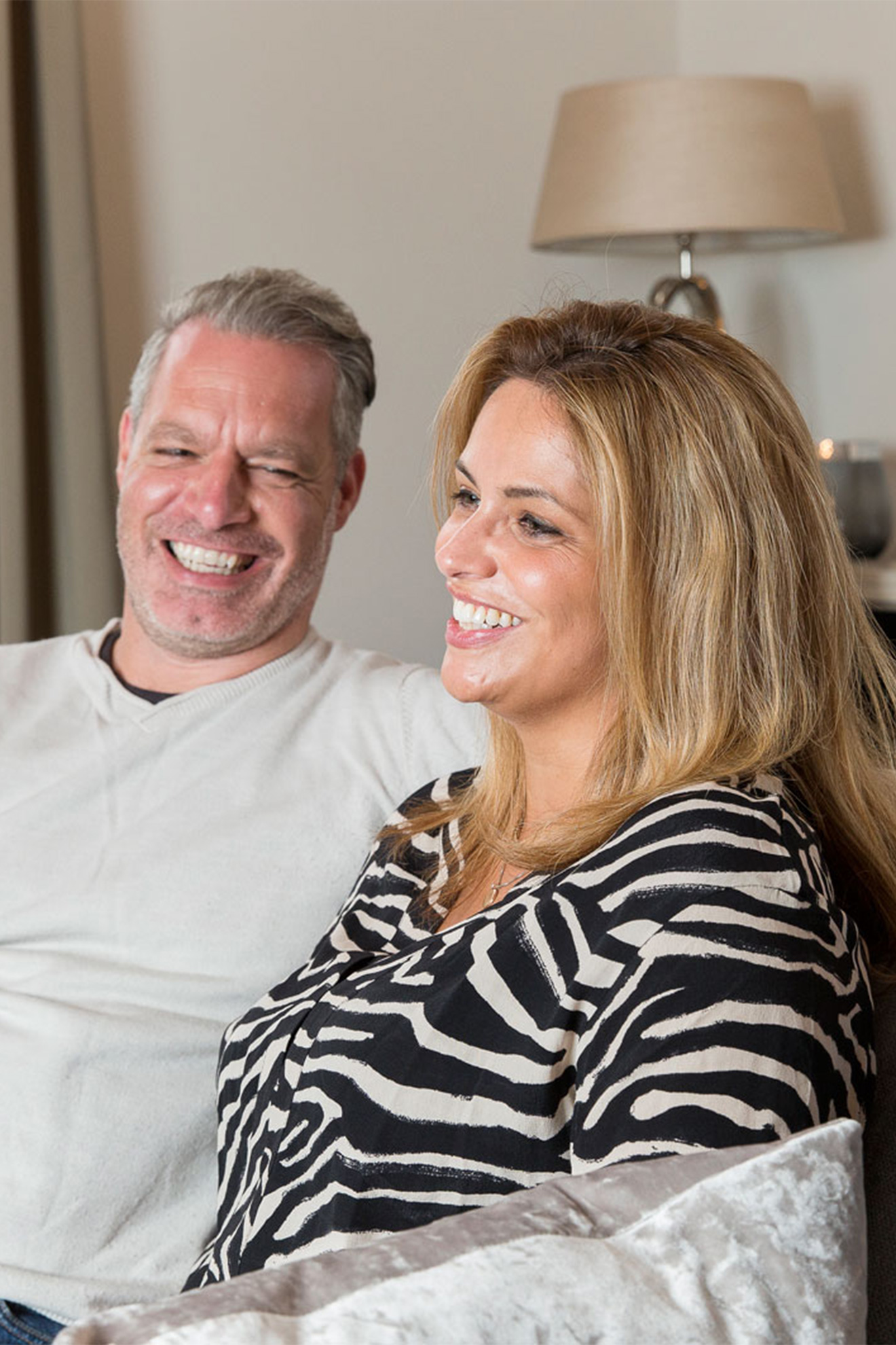 Couple laughing on a sofa.
